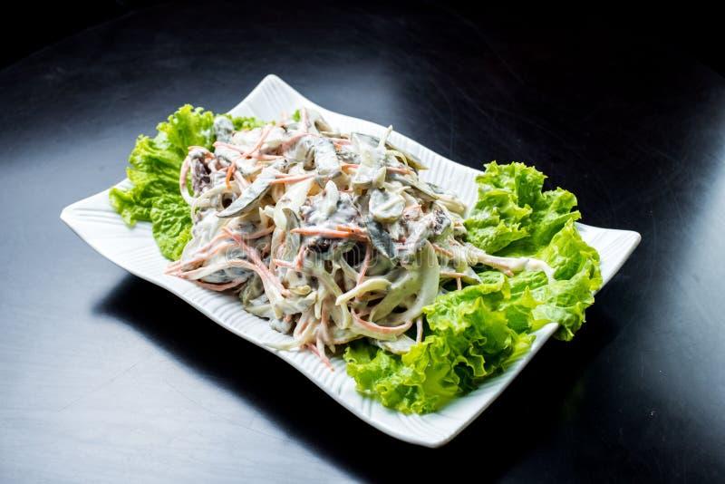 Chińska kuchnia, sałatka z pieczarkami, smażył wołowinę, zalewy, sałata w białym talerzu na czarnym tle obraz royalty free