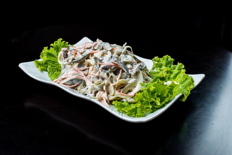 Chińska kuchnia, sałatka z pieczarkami, smażył wołowinę, zalewy, sałata w białym talerzu na czarnym tle zdjęcia stock