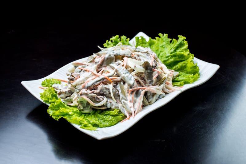 Chińska kuchnia, sałatka z pieczarkami, smażył wołowinę, zalewy, sałata w białym talerzu na czarnym tle obraz stock
