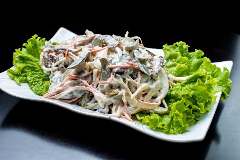 Chińska kuchnia, sałatka z pieczarkami, smażył wołowinę, zalewy, sałata w białym talerzu na czarnym tle obrazy stock