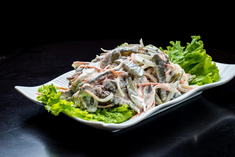 Chińska kuchnia, sałatka z pieczarkami, smażył wołowinę, zalewy, sałata w białym talerzu na czarnym tle zdjęcia royalty free