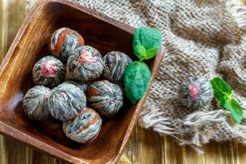 Chińska kwitnąca herbata i sprig mennica w drewnianym pucharze zdjęcia royalty free