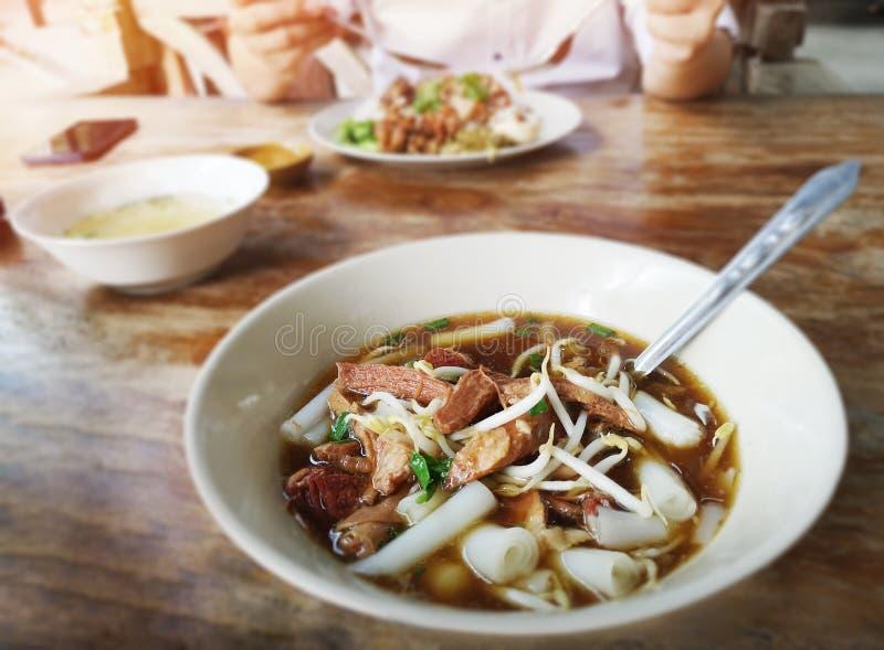 Chińska rolka kluski polewka W białym pucharze na stole atmosfera w ulicznej karmowej restauracji zdjęcie stock