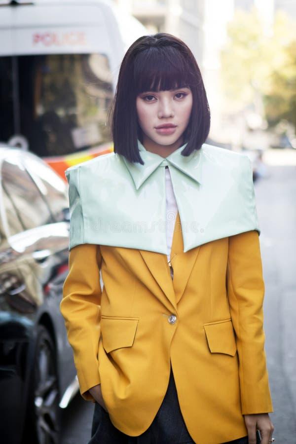 Chiński blogger w żółtej kurtki i zieleni przylądku zdjęcie stock