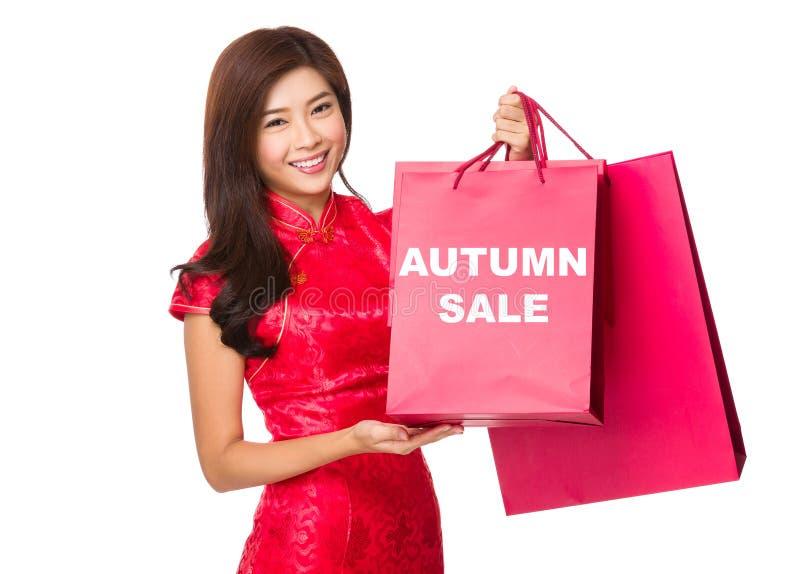 Chiński kobieta chwyt z czerwoną papierową torbą i pokazywać jesieni sprzedaż obraz stock