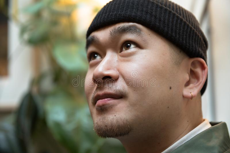 Chiński młody człowiek z kolczykiem przeciw zielonej rośliny tłu obrazy royalty free