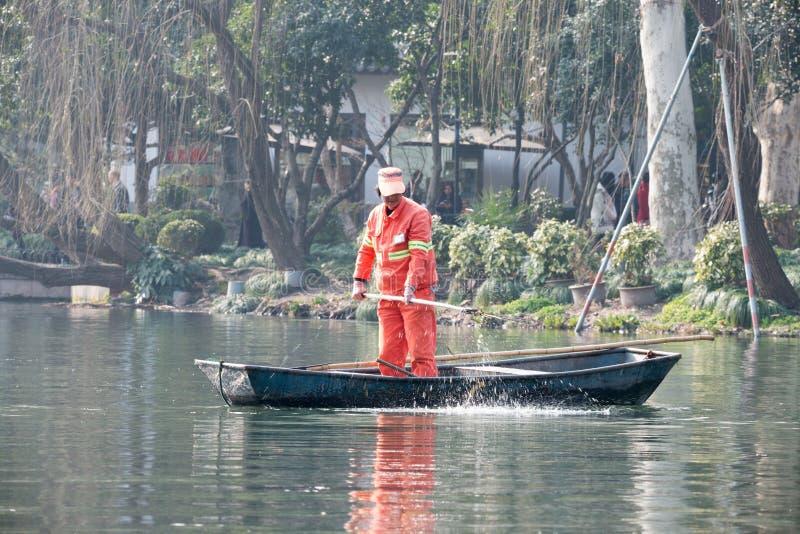 Chiński pracownika cleaning opuszcza od jeziora ręką, dzień, łódź, stoi zdjęcie stock