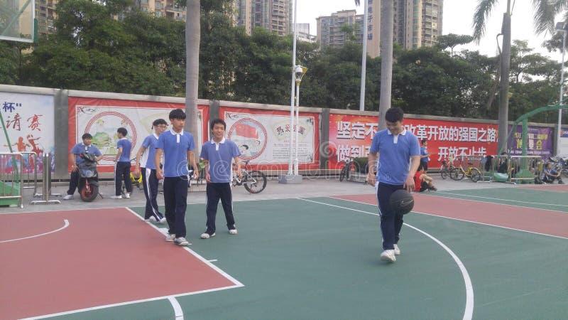 Chińskie szkół średnich chłopiec bawić się koszykówkę przy centrum sportowego boisko do koszykówki obrazy stock