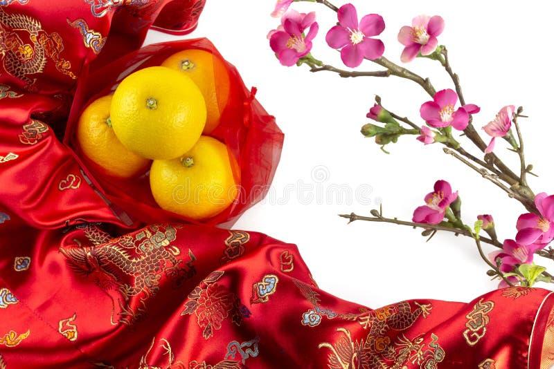 Chińskiego nowego roku świeże pomarańcze na czerwonej Chińskiej tkaniny i czereśniowego okwitnięcia gałąź graniczą na białym tle zdjęcie royalty free