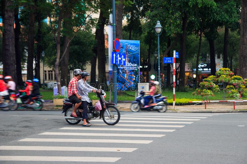 Ho Chi Minh city, Vietnam - December 2018: motorbike with tow people stopped on the crosswalk near the park. royalty free stock images