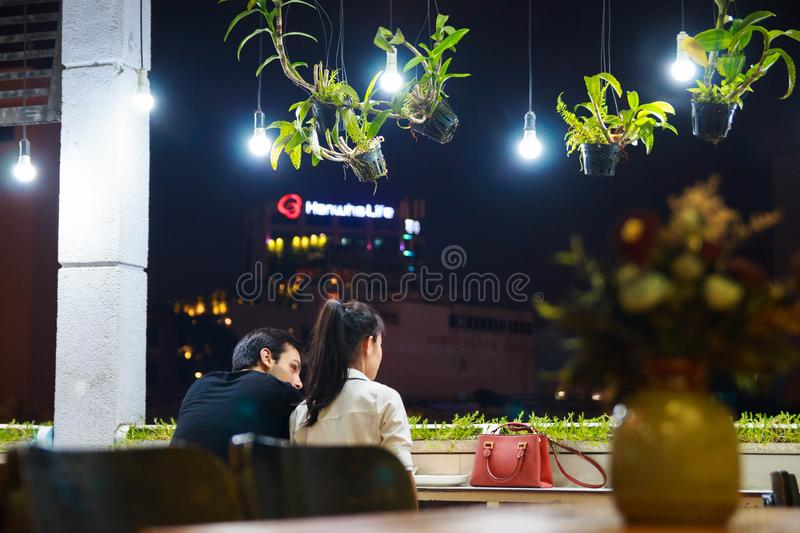 Ho Chi Minh city, Vietnam - December 2018: couple seats on the balcony of cozy cafe with lanterns and green plants. royalty free stock photo
