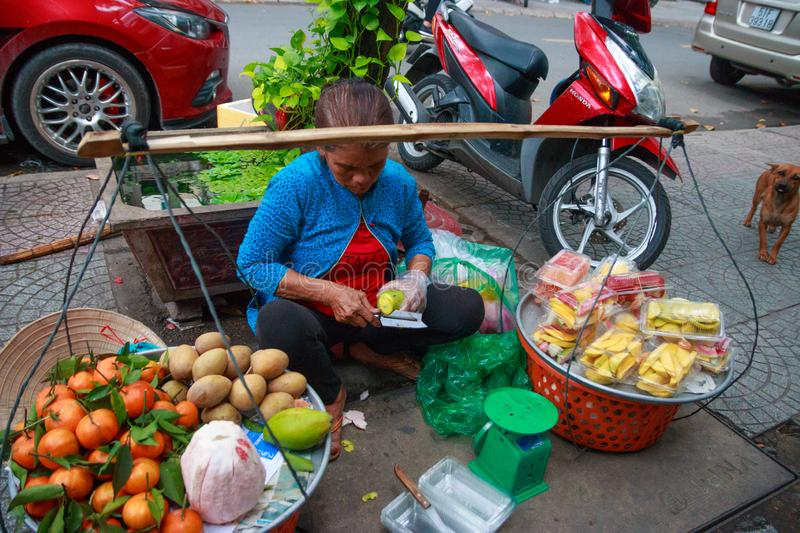 Ho Chi Minh city, Vietnam - December 2018: woman sells fresh fruits on a street of the city. royalty free stock photo