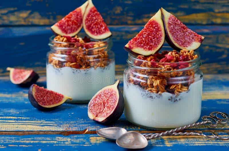 Chia与格兰诺拉麦片和新鲜的切的无花果的牛奶布丁在蓝色木厨房用桌上的玻璃瓶子与葡萄酒匙子 库存照片