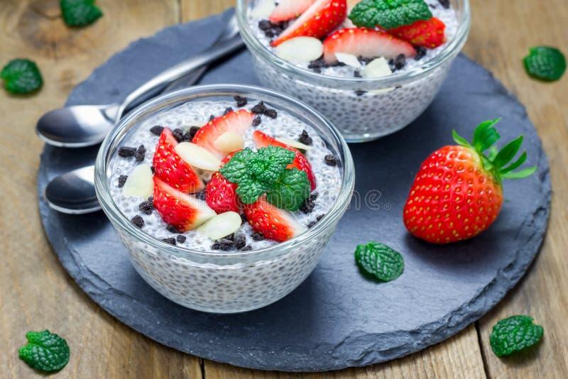 Chia种子布丁用草莓、杏仁和巧克力曲奇饼捏碎 免版税库存图片