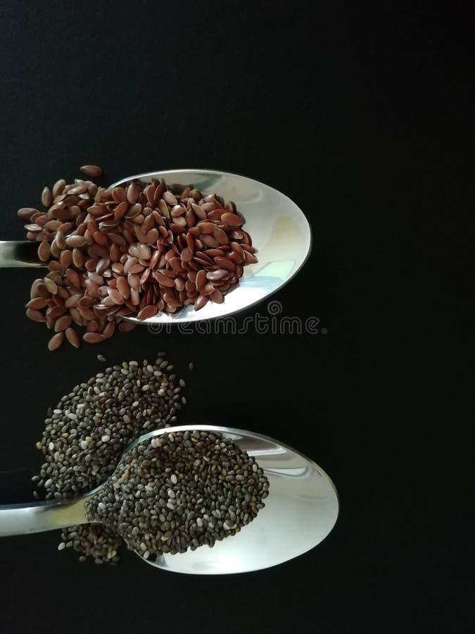 Chia e sementes de linho na colher da em um fundo preto Copie o espa?o imagens de stock royalty free