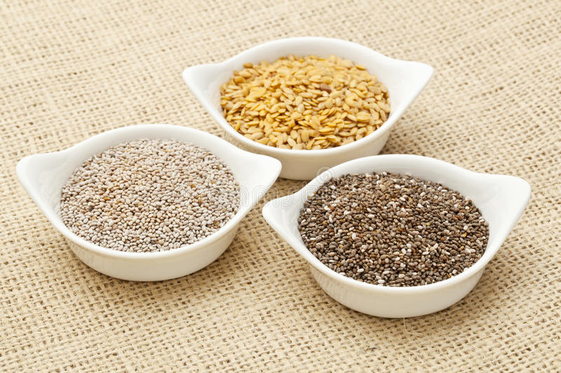 Chia and flax seed. White and brown chia and golden flax seed in white ceramic bowls against burlap canvas royalty free stock photo