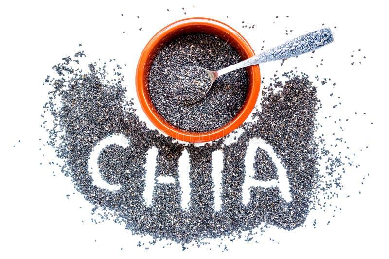 Chia frö i en keramisk bunke och en liten silversked royaltyfria foton