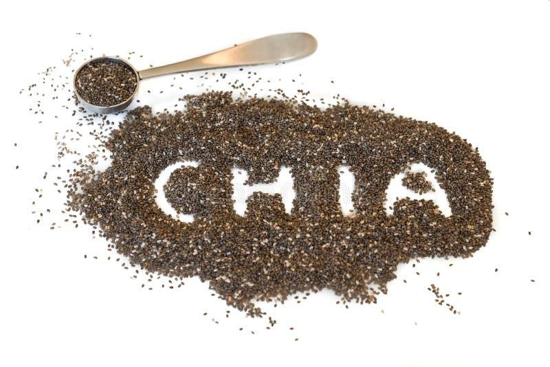 Chia frö spritt på en vit bakgrund med ordchiaen stavade ut, och en metalltesked arkivbild
