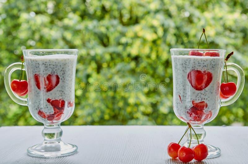 Chia-Milchpudding mit geschnittenen Erdbeeren und Kirschen in den Gläsern Sommer Detox superfoods Frühstück oder gesunder Nachtis stockbilder