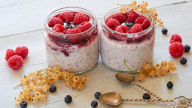 Chia milk pudding with fresh raspberry in the glass jars on the gray kitchen table. Summer detox superfoods breakfast. Or healthy dessert. Close up view royalty free stock photography