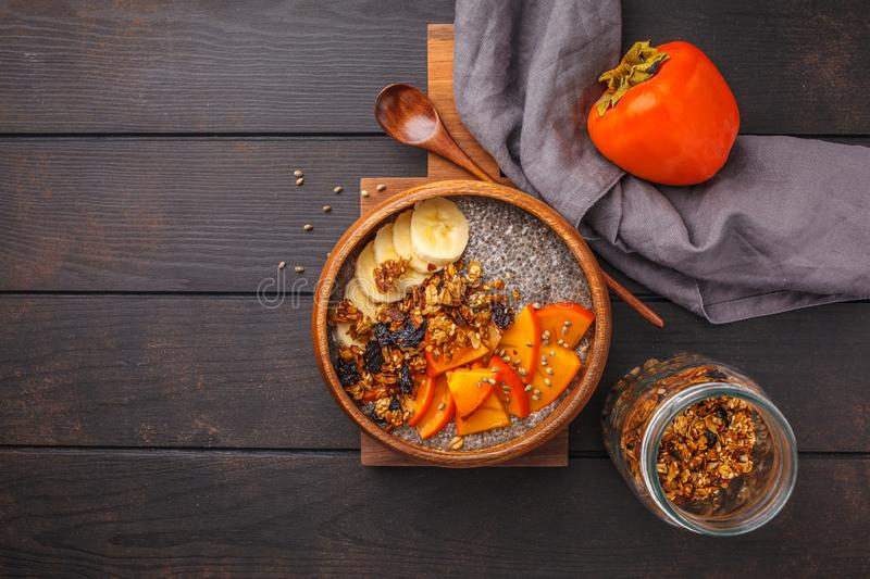 Chia pudding with banana, persimmon and granola, dark wooden background, top view, copy space. royalty free stock images