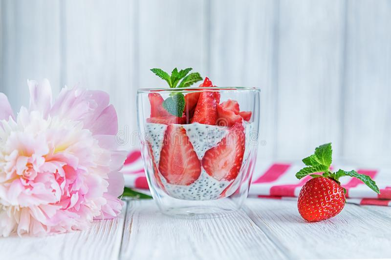 Chia pudding with fresh strawberries and mint in glass on white background. Summertime royalty free stock photos