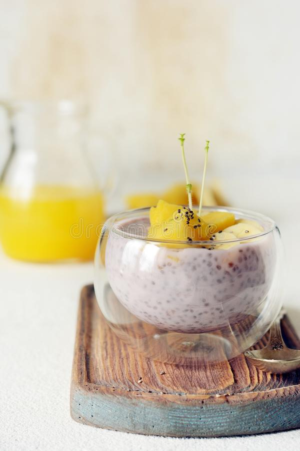 Chia pudding with mango pulp in beautiful glasses with green mint leaves and cut fresh ripe tropical fruit, orange juice. For breakfast on a light background stock photos