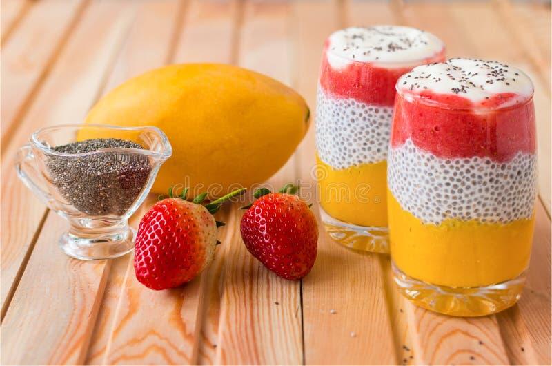 Chia pudding med mango, naturlig yoghurt, lös jordgubbe i ett exponeringsglas på en trätabell Sund efterrätt, toppen mat arkivfoton