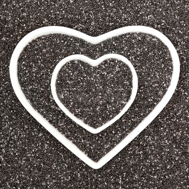Chia Seed. Health food in heart shaped porcelain bowls forming an abstract background. Salvia hispanica stock image