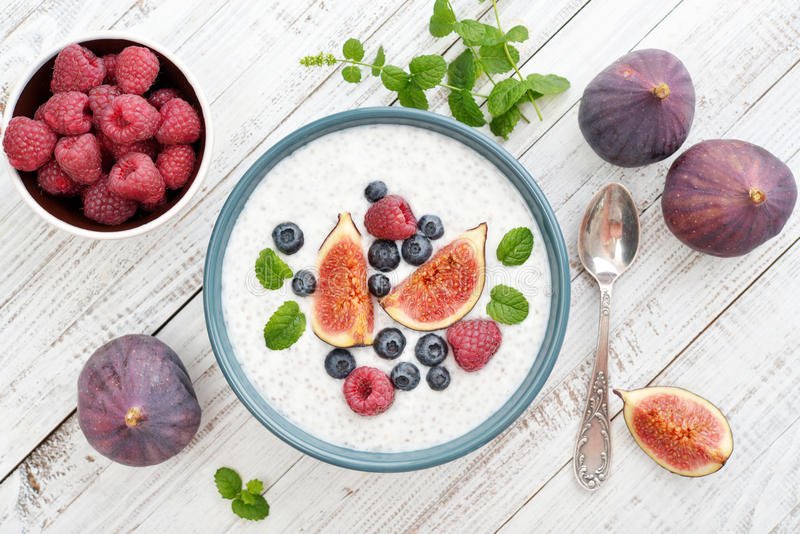 Chia seed pudding. With figs, raspberry and blueberries in bowl on wooden background, top view royalty free stock photos