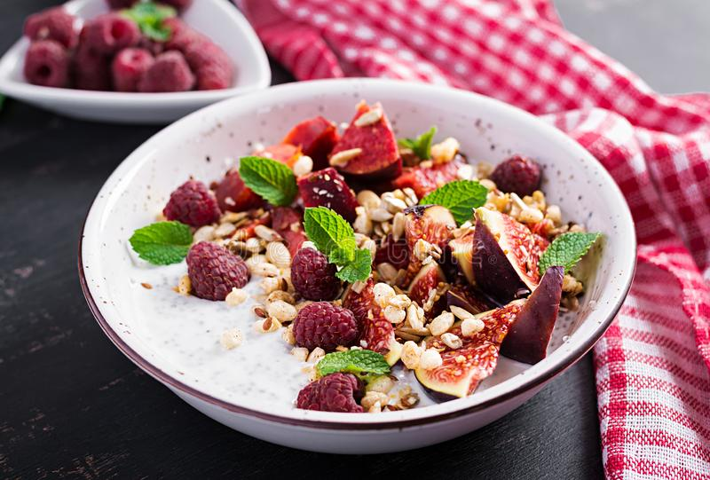 Chia seed pudding made with raspberries, figs and mint on dark background. stock photo