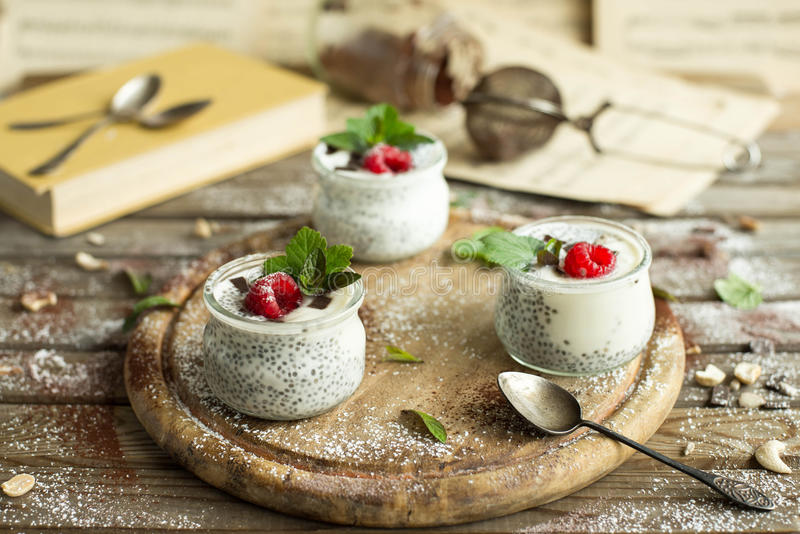 Chia seed pudding with raspberries chocolate and mint in jars. Close up stock image
