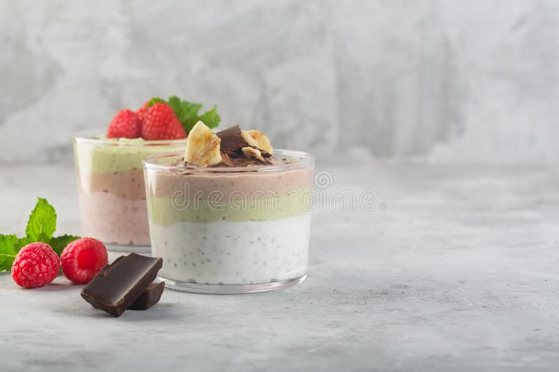 Chia seed pudding with three flavors, cocoa, matcha and strawberry with yoghurt, chocolate and mint leaves. Copy space royalty free stock photo