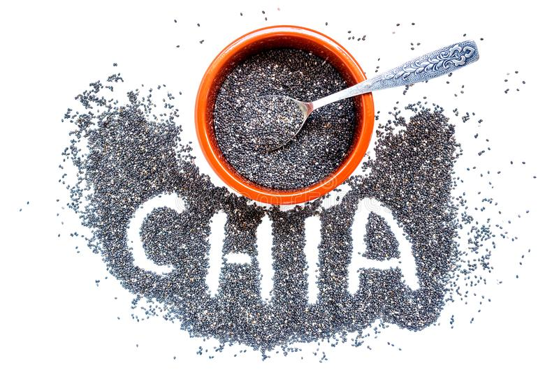 Chia seeds in a ceramic bowl and a small silver spoon. royalty free stock photos