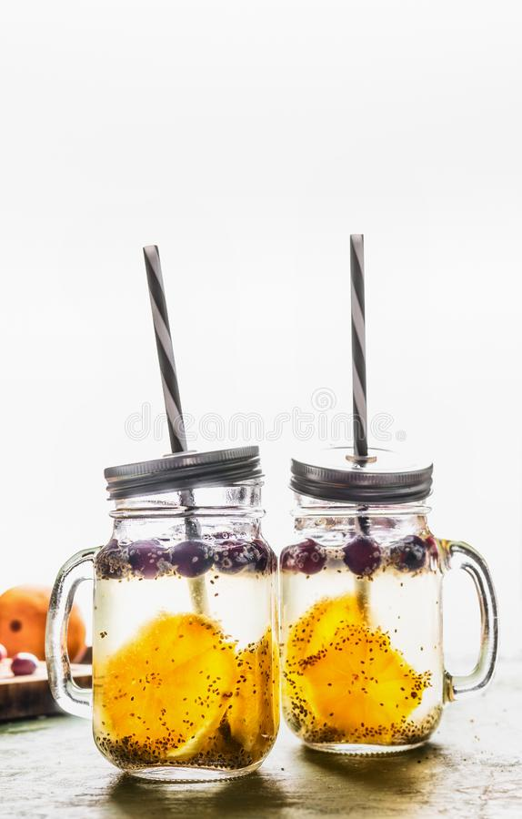 Chia seeds water in Mason jars with orange slices and berries. Natural detox energy drink.  Proper nutrition, healthy supplements. Transparent drink stock photography