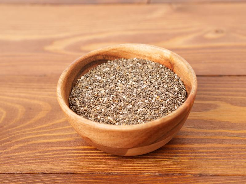 Chia seeds in wooden bowl on brown wooden background, side view. Chia seeds in wooden bowl on a brown wooden background, side view royalty free stock image