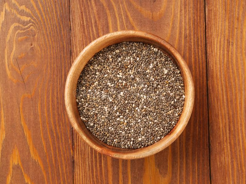 Chia seeds in wooden bowl on brown wooden background, top view. Chia seeds in wooden bowl on a brown wooden background, top view stock photography