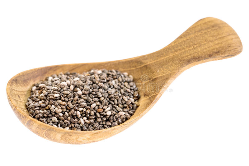 Chia seeds on wooden tablespoon. Chia seeds on a small wooden tablespoon isolated on white, selective focus royalty free stock photos