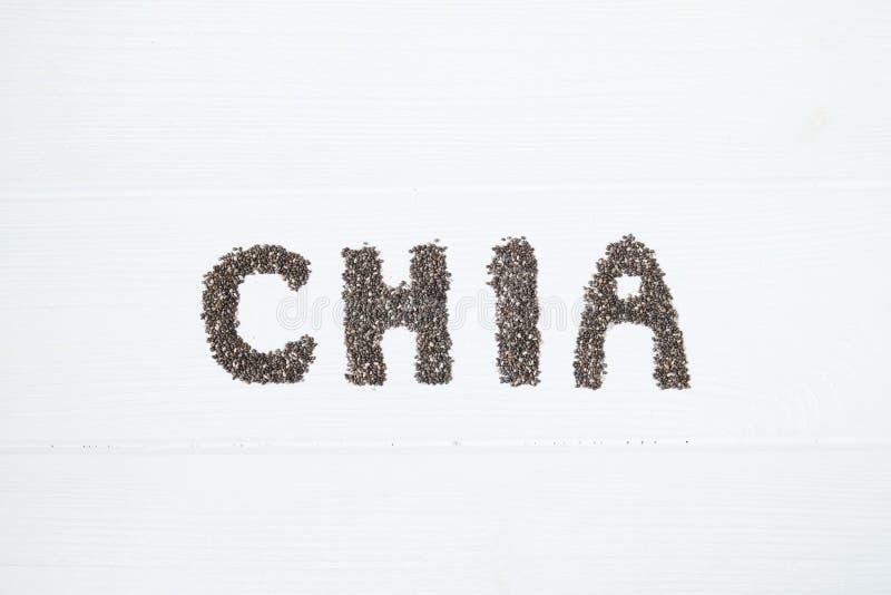 Chia Startwerte für Zufallsgenerator Chia-Wort gemacht von chia Samen mit dem Löffel voll vom chia in einer Schüssel lizenzfreies stockbild