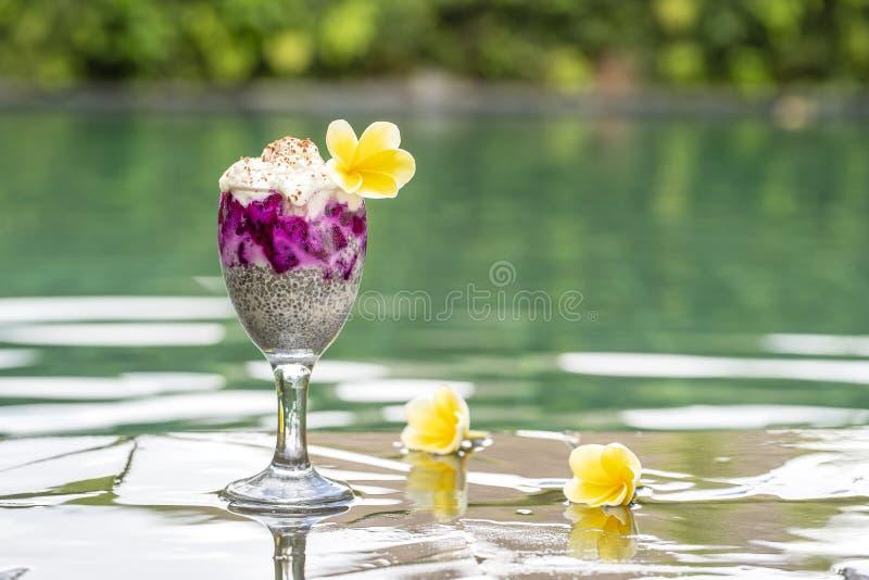 Chia ziaren pudding z czerwoną smok owoc i biały jogurt w szkle dla śniadania na tle basen woda fotografia stock