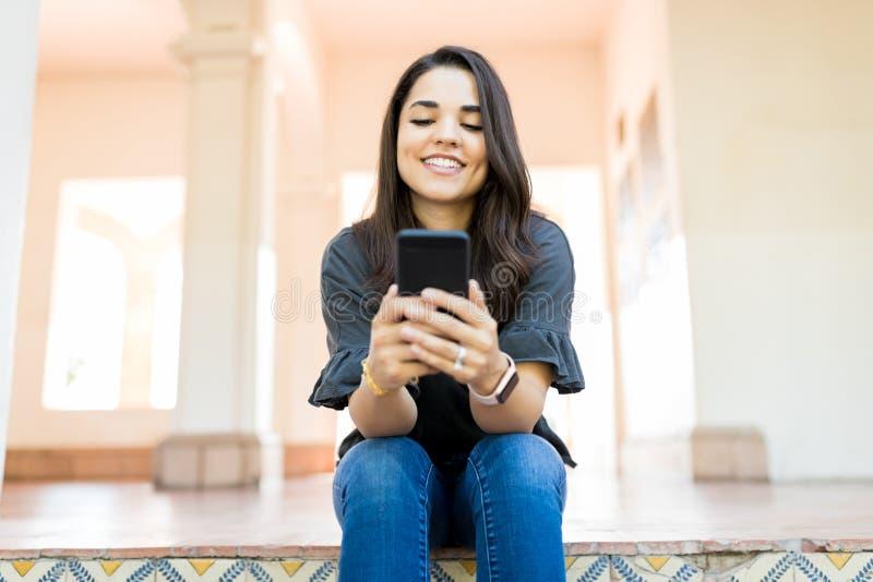 Chiacchierata femminile sui media sociali sul corridoio immagini stock