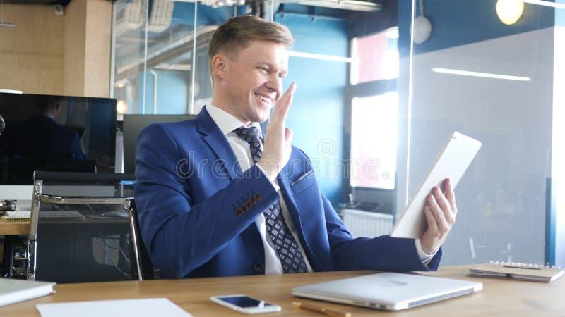 Chiacchierata online di Saying Hello During dell'uomo d'affari video sulla compressa immagine stock libera da diritti