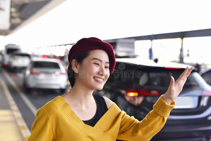 Chiamata asiatica della donna un servizio dell'automobile del taxi all'aeroporto fotografia stock libera da diritti