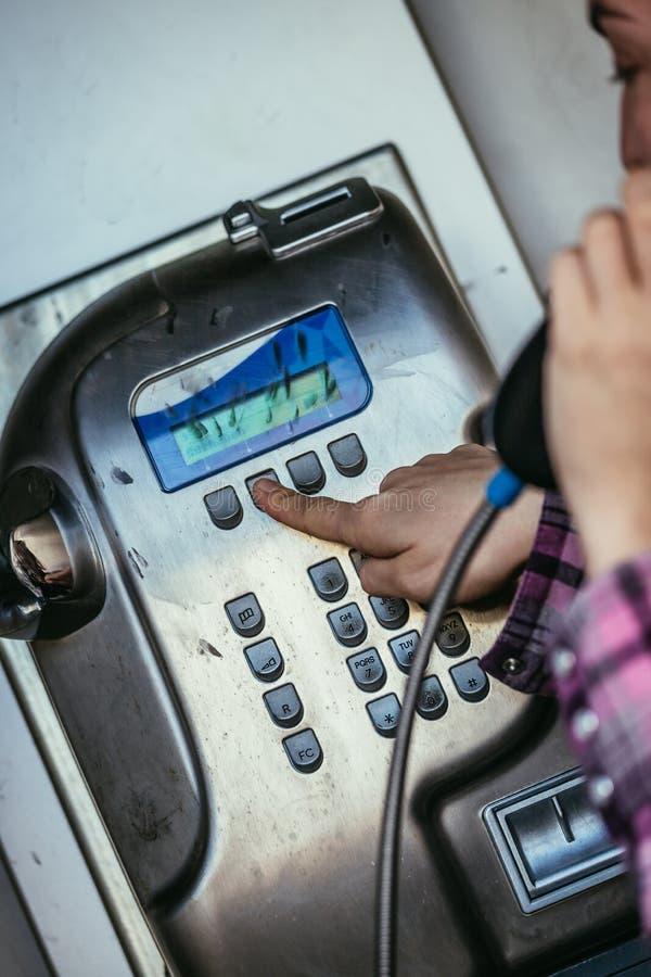 Chiamata a casa nelle feste: La ragazza parla in un telefono di paga antiquato immagine stock libera da diritti