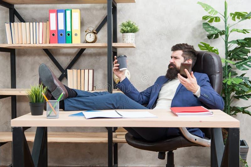Chiamata mobile Giorno di inizio con caffè Rottura di rilassamento del caffè Tazza e smartphone barbuti della tenuta dell'uomo d' immagine stock libera da diritti