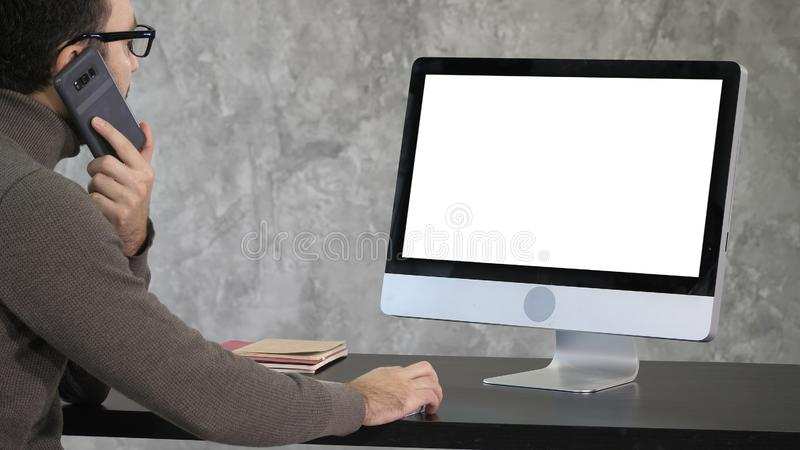 Chiamate maschii concentrate serie dell'impiegato di concetto con il suo telefono ed impianti sul computer Visualizzazione bianca fotografia stock libera da diritti