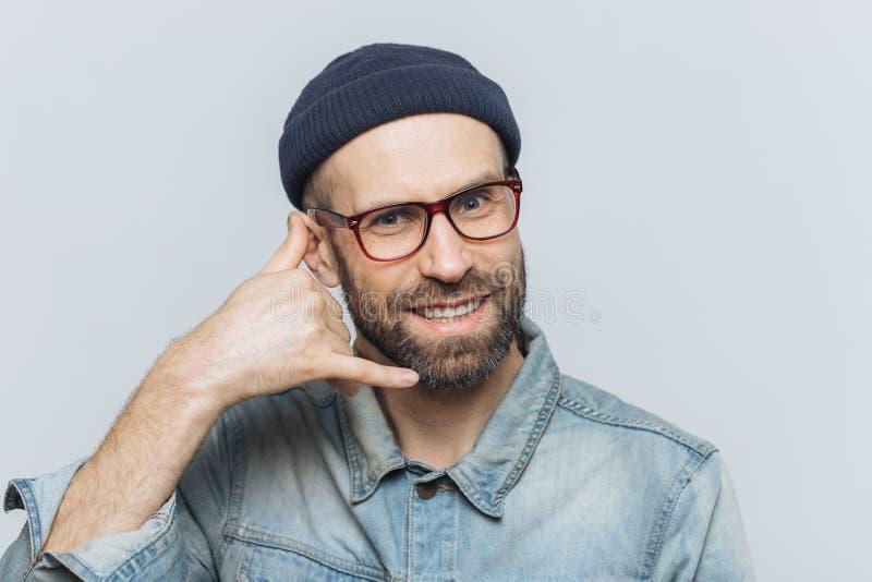 Chiamimi per favore! L'uomo bello felice tiene la mano vicino all'orecchio, imita la conversazione di telefono cellulare, sorride fotografia stock libera da diritti