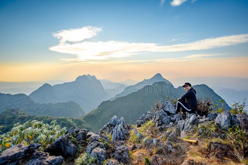 Asian Backpackers trekking waiting golden sunset sky stock photography