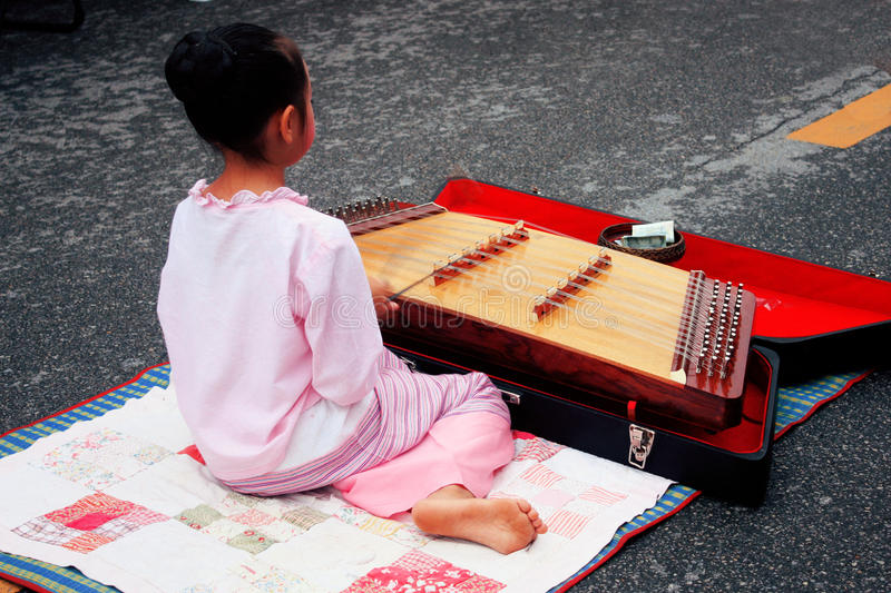 Chiang Mai girl. Children playing music in the Chiang Mai market (Thailand royalty free stock image