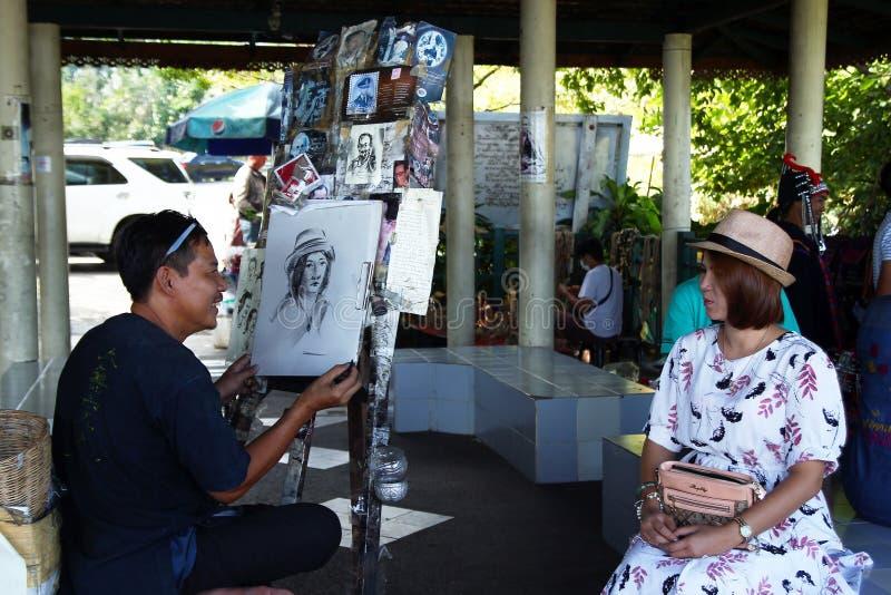 Chiang Mai, Tailândia - 3 de dezembro de 2017: O artista desconhecido da rua está tirando o retrato da mulher imagem de stock royalty free